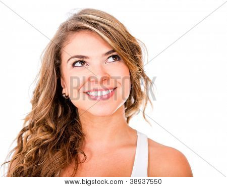 Thoughtful woman smiling and looking up - isolated over white