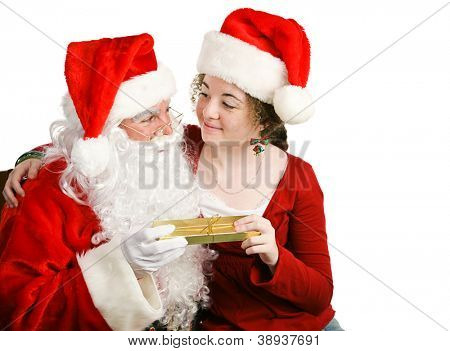 Girl sitting on Santa Claus' lap, getting a Christmas present from him.  Isolated on white.