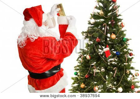 Santa Claus hard at work stuffing stockings for Christmas morning.  Isolated on white.