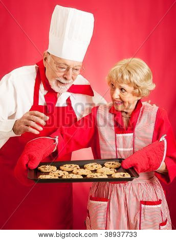 Chef admires the delicious chocolate chip cookies baked by a homemaker.
