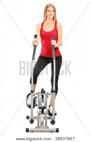 Full length portrait of a female athlete standing on a cross trainer machine isolated on white background