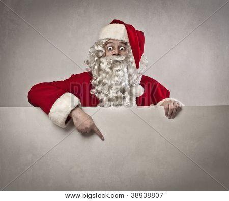 Santa Claus indicating something a white poster