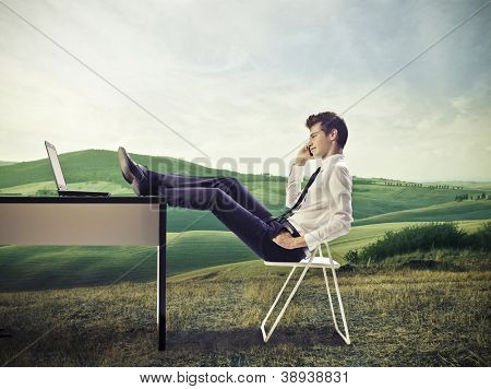 Young businessman calling. in a large grace field, with his feet on his desk