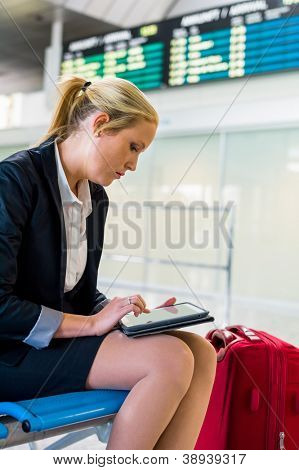 a businesswoman with suitcase and tablet computer at an airport. mobility and communication in business. roaming charges when abroad