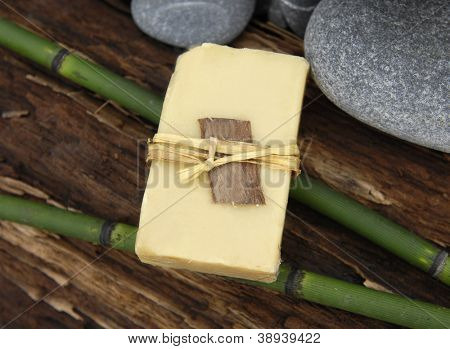 handmade soap and stones with bamboo grove on driftwood texture