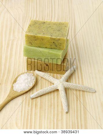 Wooden spoon with salt in bowl and three nature soap, starfish on wooden board