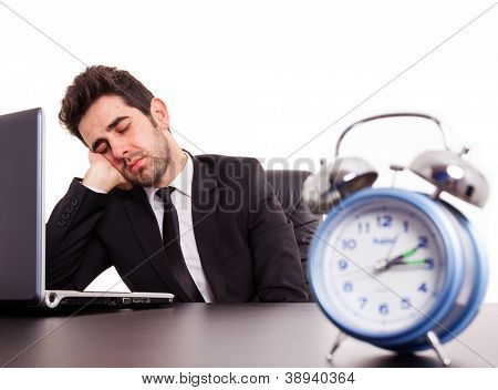Tired young businessman sleeping next laptop on white background