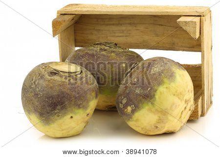 fresh turnip(brassica rape rapa) in a wooden crate on a white background