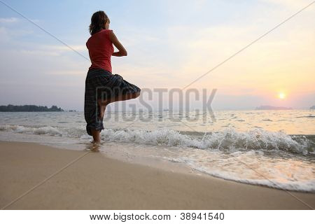 Young woman relaxing on a beach at sunset