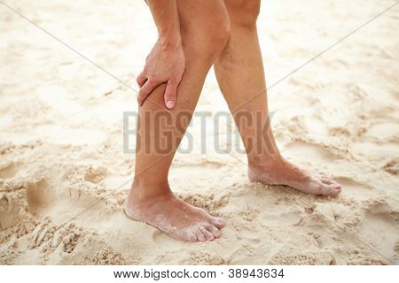 Woman legs pain with cramp on the beach.