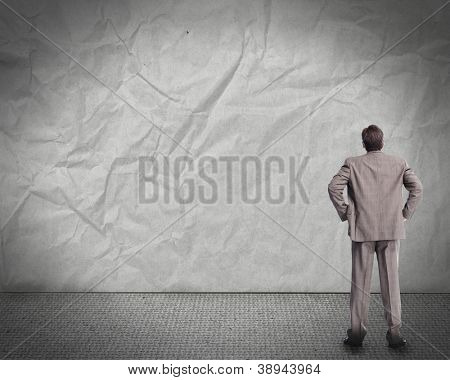 Businessman looking at the wall. Abstract background.