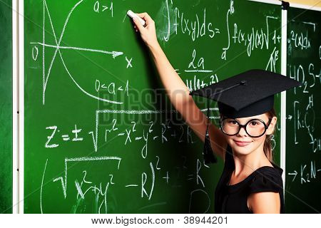 Portrait of a cute schoolgirl in academic hat and big round spectacles at a classroom.