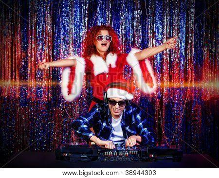 Homem de DJ mistura-se alguma alegria de Natal com a donzela de neve atraente. Luzes de discoteca em segundo plano.