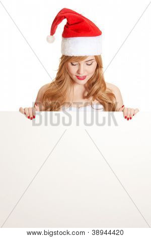 Xmas pretty woman peeking from behind blank sign billboard isolated