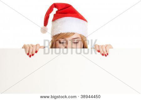Xmas pretty woman peeking from behind blank sign billboard isolated