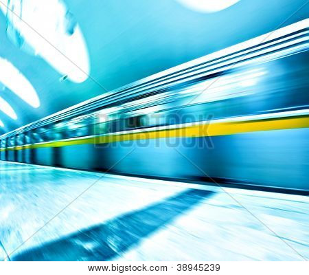 Perspective wide angle view of modern light blue illuminated and spacious public metro marble station with fast blurred trail of train in vanishing traffic motion