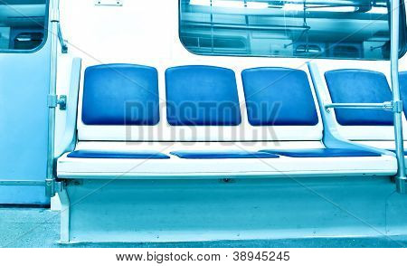 Contemporary light blue illuminated carriage interior with nobody of people inside underground metro station