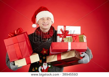 Portrait of happy man in Santa cap with giftboxes looking at camera