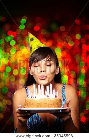 Portrait of pretty girl holding birthday cake and blowing candles at party