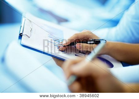 Close-up of businesswoman hand with document writing at lecture