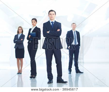 Portrait of young businessman looking at camera with elegant partners on background
