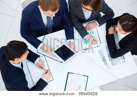 Gruppe von Geschäftspartnern betrachten Touchscreen während Planungsarbeiten Tagung