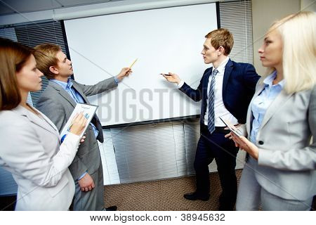 Two confident businessmen pointing at whiteboard while making speech at meeting