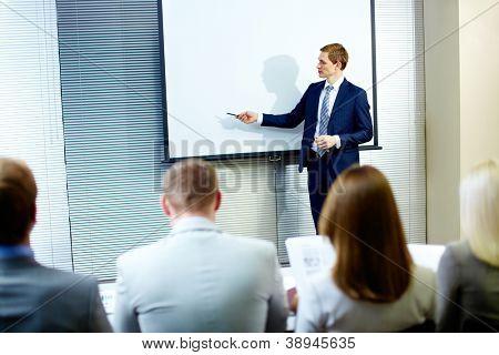Seguro empresario apuntando en la pizarra mientras habla en Conferencia