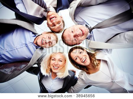 Below view of several happy business partners looking at camera while embracing each other