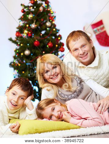 Portrait of four happy family members at home on Christmas Eve