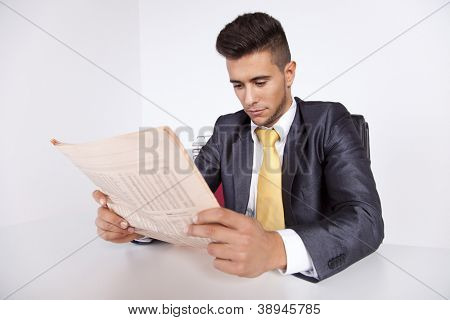 Businessman reading the newspaper in his office