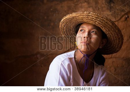 Traditional Myanmar girl in straw hot is looking away