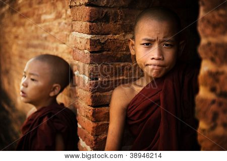 Two young buddhist novice monk outside a temple background.