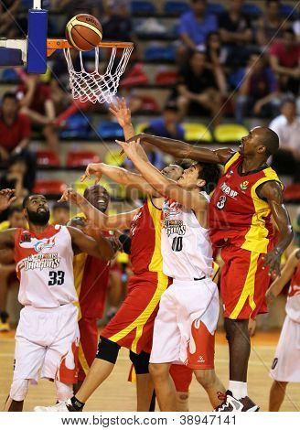 KUALA LUMPUR - OCTOBER 27: Farmcochem's player (red) and Dragons players (white) scramble for a loose ball in a Malaysia National Basketball League match on October 27, 2012 in Kuala Lumpur, Malaysia.