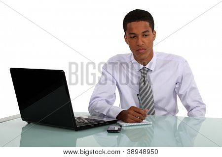 Man sat at desk writing on pad