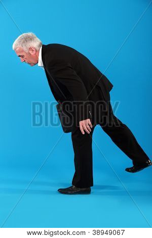 Old businessman struggling to stay in his feet