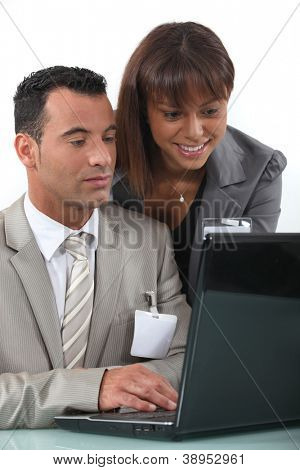 Two flirtatious businesspeople working together