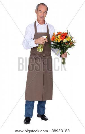 Florist spraying a bouquet of flowers