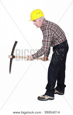 A mature construction worker using a pickaxe.