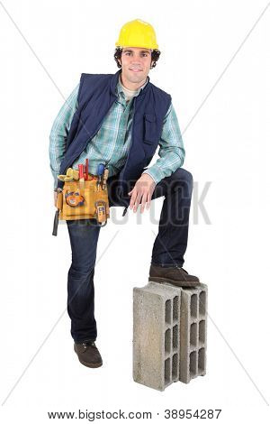 Man resting foot on building block