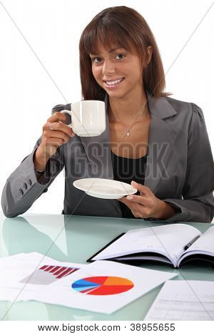 Woman having a cup of coffee at her desk