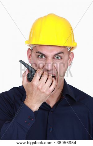 angry businessman wearing helmet and shouting on a walkie talkie