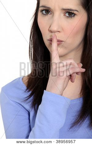 Angry woman holding her finger to her lips