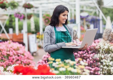 Woman doing stocktaking with laptop in garden centre
