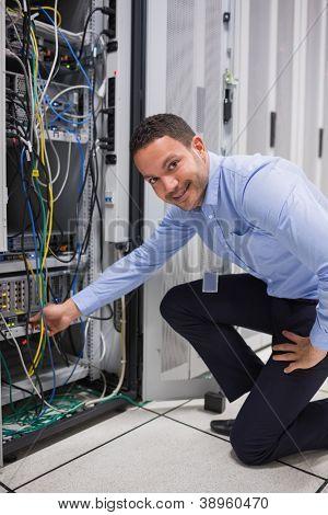 Lächelnder Mann anpassen Kabel auf dem Server im Rechenzentrum