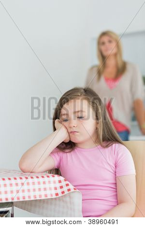 Little girl is sitting while looking exasperated at kitchen table wth mother in background
