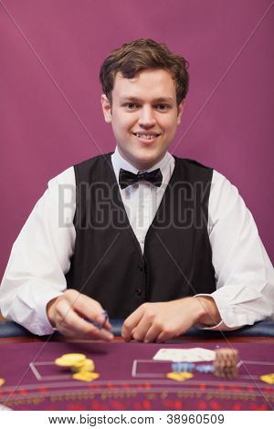 Dealer sitting at table in a casino while distributing chips