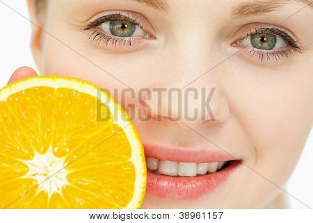 Close up of a woman placing an orange near her lips against white background