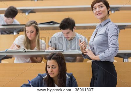 Students working while teacher smiling in lecture hall