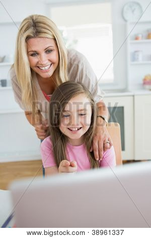 Little girl pointing at laptop and laughing with mother in the kitchen